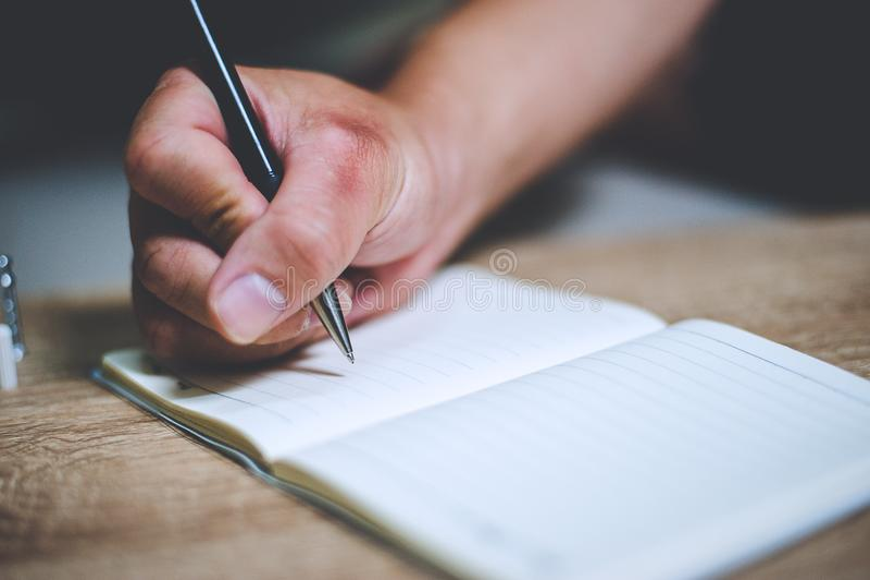 Homem de negócios que escreve uma nota de livro que toma a nota que toma o conceito imagem de stock royalty free
