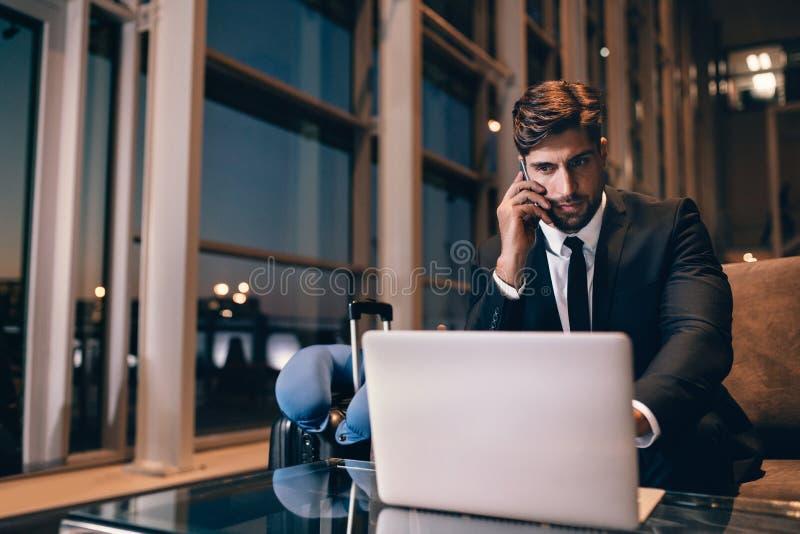 Homem de negócios que espera seu voo na sala de estar do aeroporto foto de stock