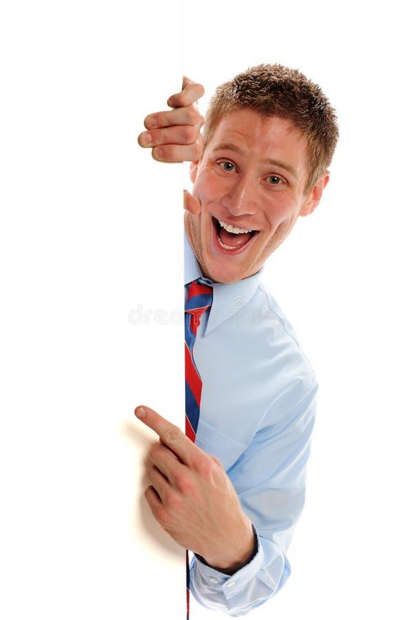 Homem de negócios que espreita em torno do sinal fotografia de stock
