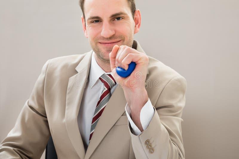 Homem de negócios que espreme o stressball azul foto de stock