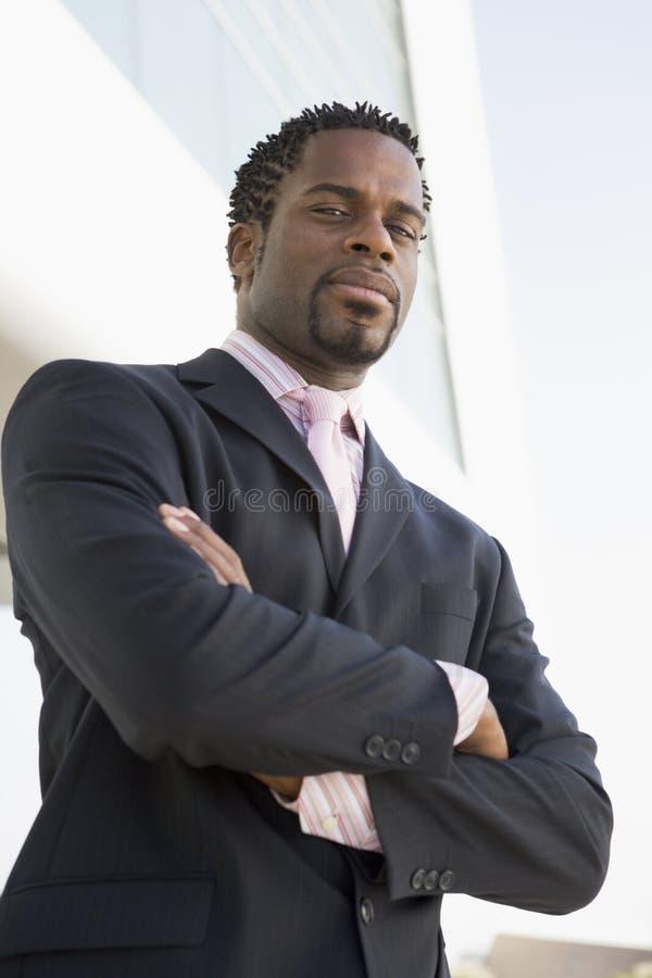 Homem de negócios que está ao ar livre pelo edifício fotografia de stock