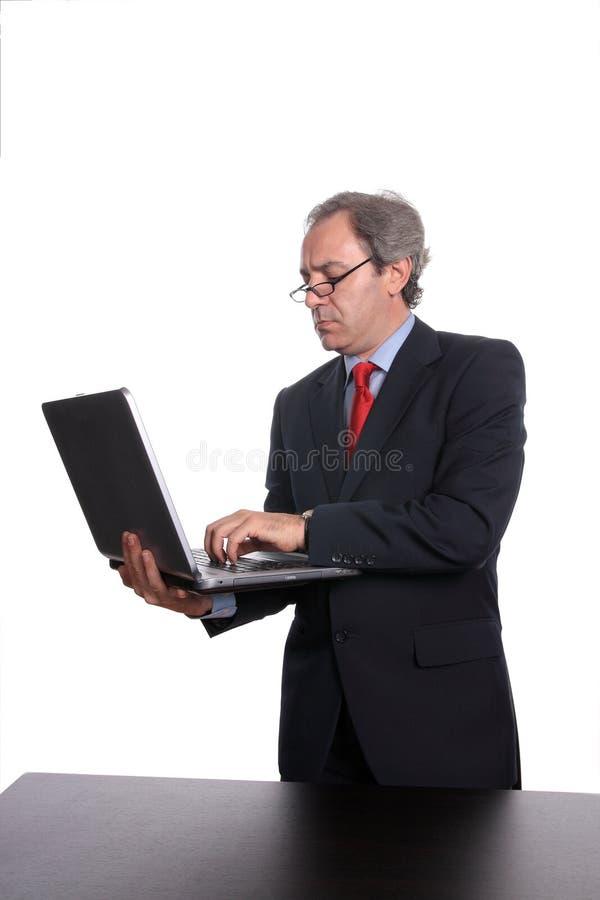 Homem de negócios que está com portátil imagens de stock
