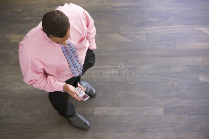 Homem de negócios que está dentro de vista o telefone imagem de stock