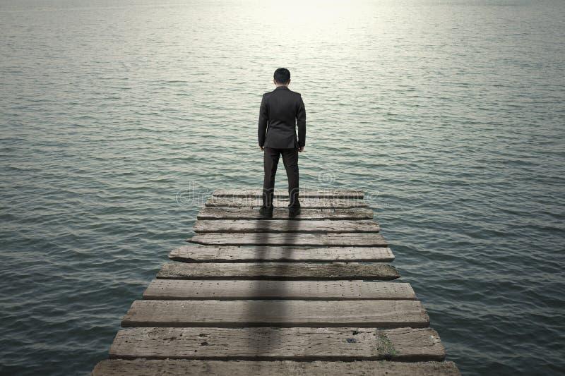 Homem de negócios que está e que pensa no cais de madeira velho ao mar foto de stock