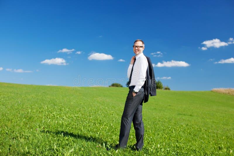 Homem de negócios que está em um campo verde imagem de stock