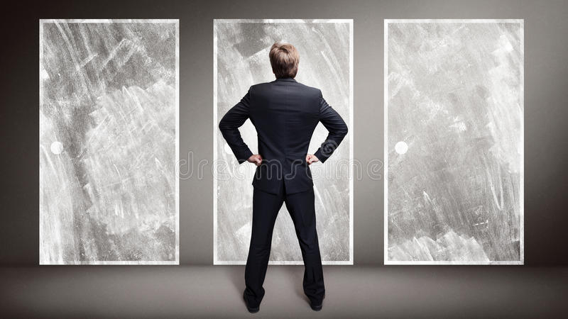 Homem de negócios que está na frente de 3 portas foto de stock