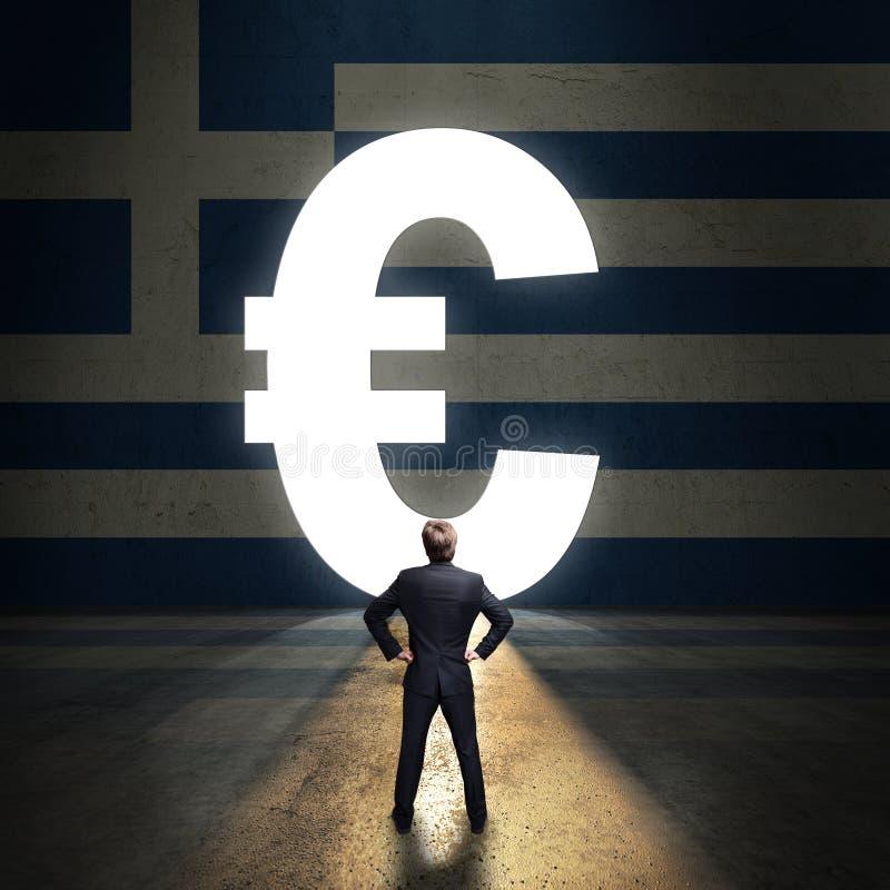 Homem de negócios que está na frente de um portal dado forma como o Euro na frente de uma parede pintada com a bandeira grega fotos de stock