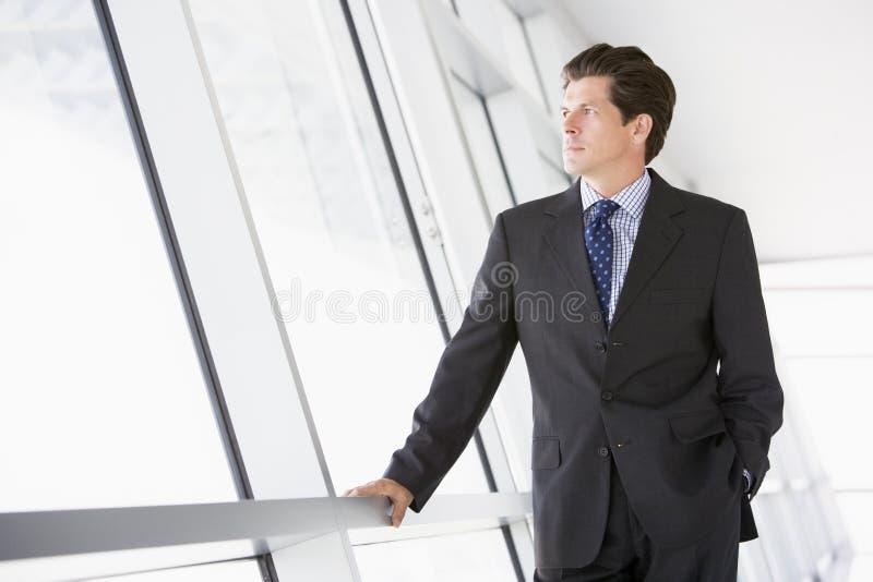 Homem de negócios que está no corredor fotografia de stock royalty free