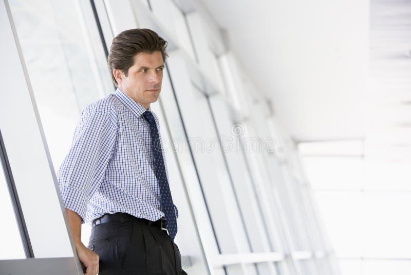 Homem de negócios que está no corredor imagem de stock royalty free