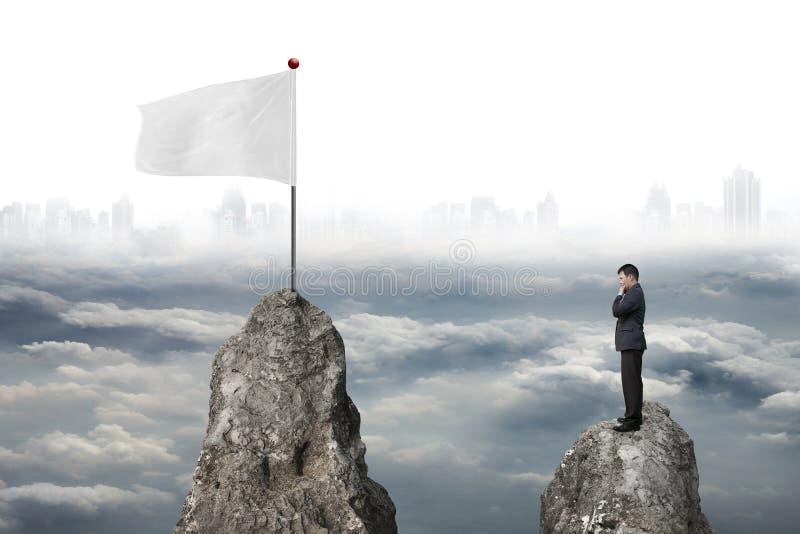 Homem de negócios que está no pico com bandeira branca e cityscap nebuloso imagens de stock royalty free