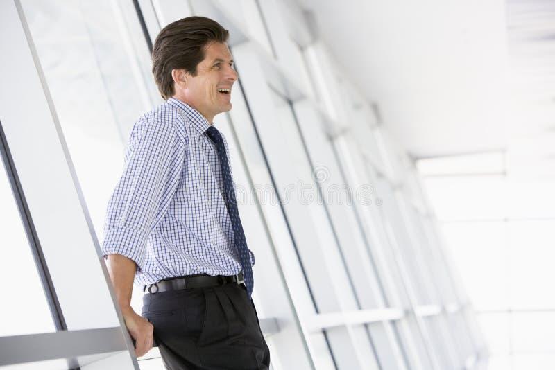 Homem de negócios que está no riso do corredor imagem de stock royalty free