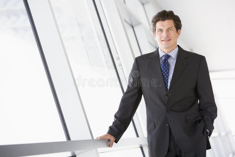 Homem de negócios que está no sorriso do corredor foto de stock
