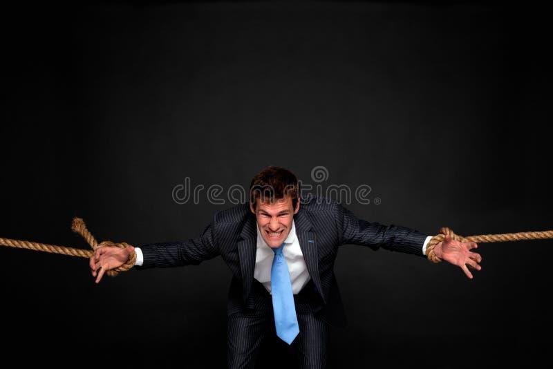 Homem de negócios que está sendo puxado pela corda em ambos os lados. imagem de stock royalty free