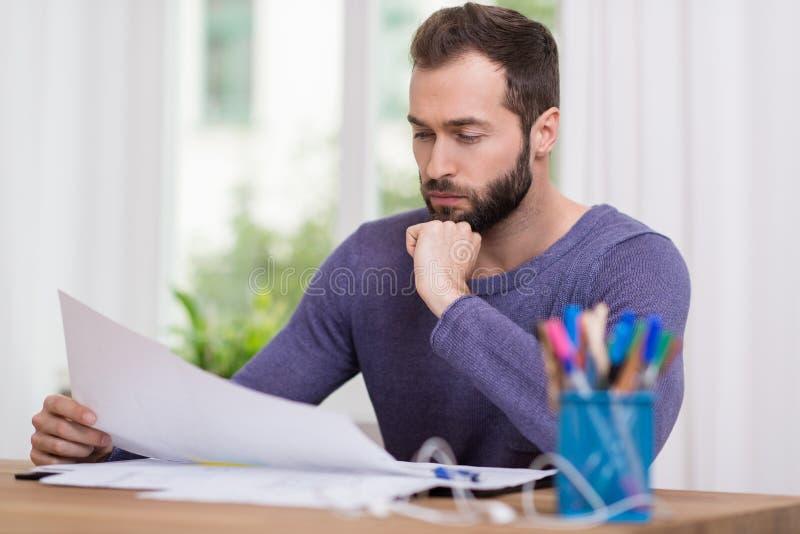 Homem de negócios que estuda um original de papel fotos de stock