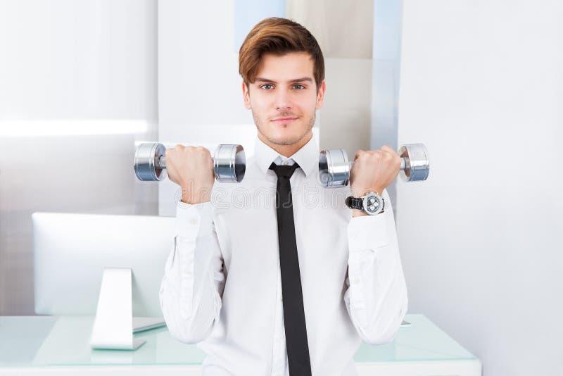 Homem de negócios que exercita com pesos fotografia de stock royalty free