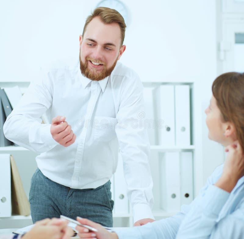 Homem de negócios que explica ideias do negócio a seus colegas Conceito do trabalho bem sucedido da equipe imagens de stock