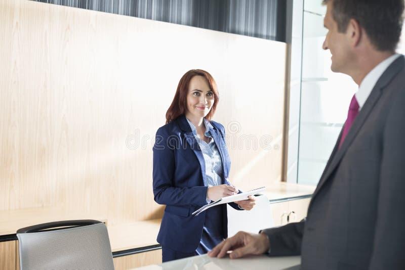 Homem de negócios que fala com o recepcionista no escritório imagens de stock royalty free