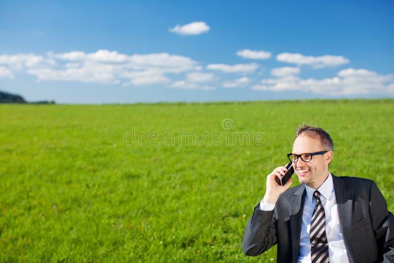 Homem de negócios que fala em seu móbil na natureza imagem de stock
