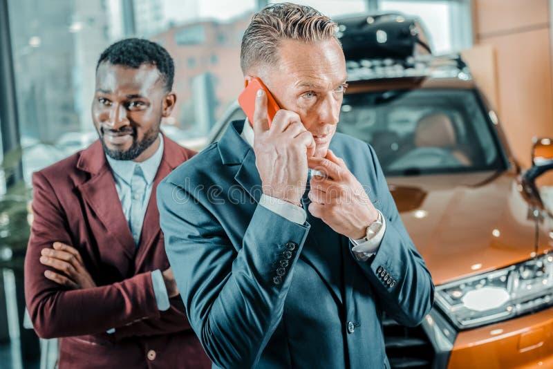 Homem de negócios que fala em seu telefone em uma sala de exposições do carro fotos de stock royalty free