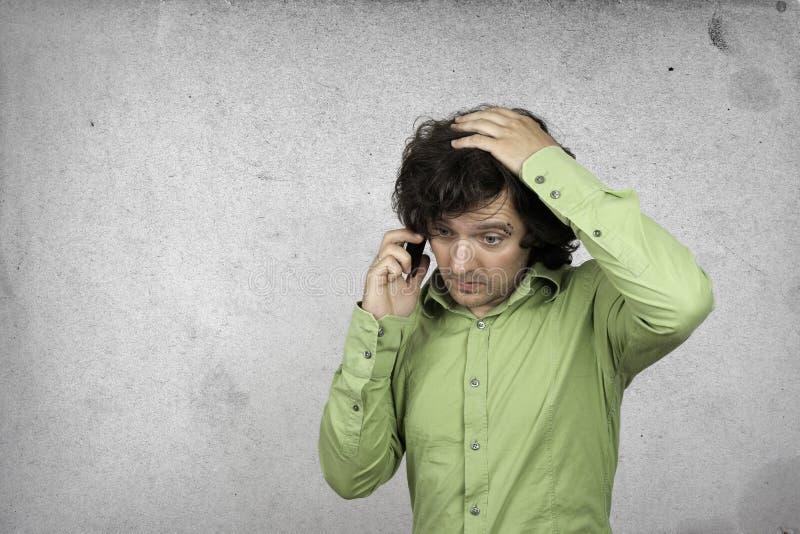 Homem de negócios que fala em um telefone celular, fundo cinzento imagens de stock