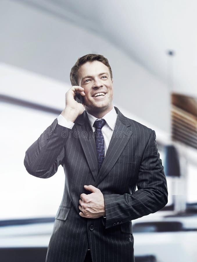 Homem de negócios que fala na posição móvel no escritório imagem de stock royalty free