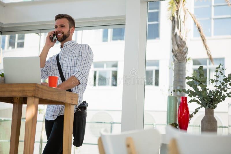 Homem de negócios que fala no telefone celular ao estar na mesa imagem de stock royalty free