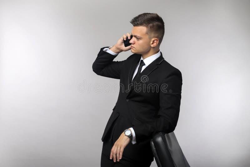 Homem de negócios que fala no telefone celular no fundo do cinza do escritório foto de stock