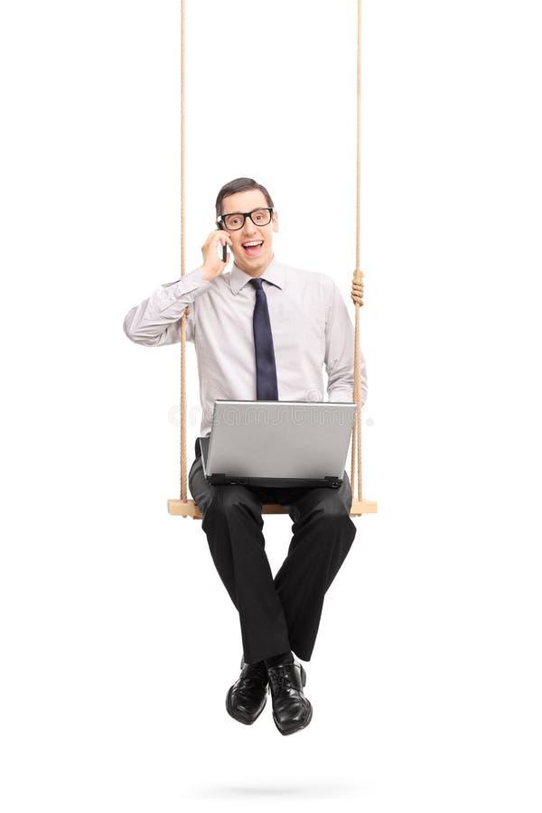 Homem de negócios que fala no telefone e no balanço foto de stock