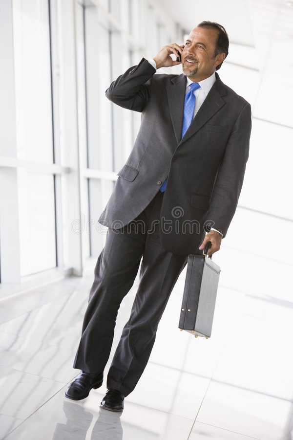 Homem de negócios que fala no telefone móvel na entrada imagens de stock