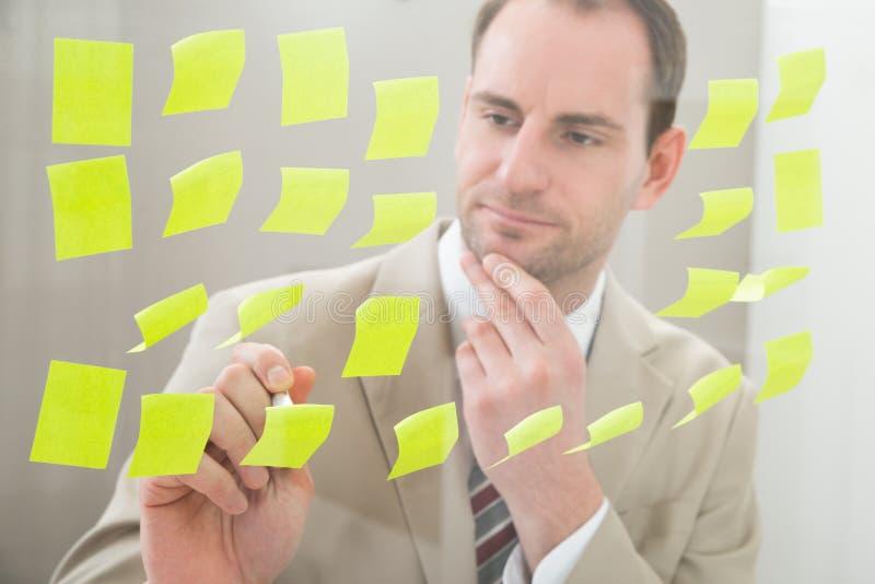 Homem de negócios que faz anotações no papel esparadrapo foto de stock royalty free