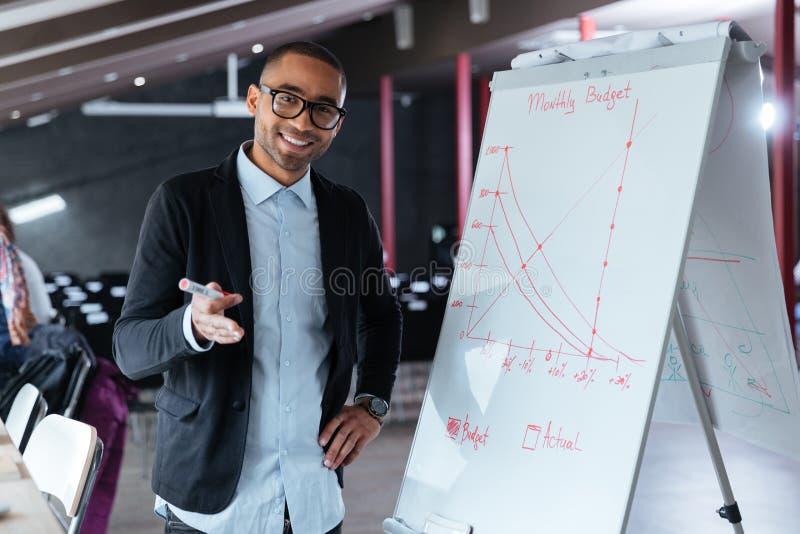 Homem de negócios que faz a apresentação usando o flipchart no escritório foto de stock royalty free