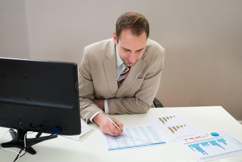 Homem de negócios que faz o diagrama de Gantt no escritório imagem de stock