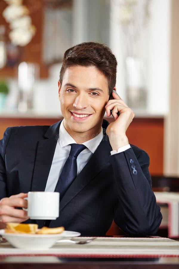 Homem de negócios que faz o telefonema na cafetaria fotografia de stock royalty free