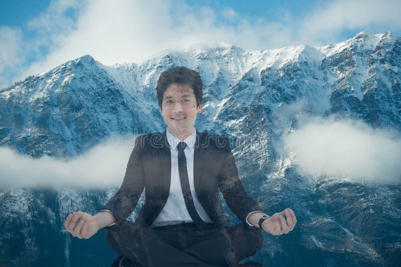 Homem de negócios que faz a posição da ioga na frente das montanhas cobertos de neve imagens de stock royalty free