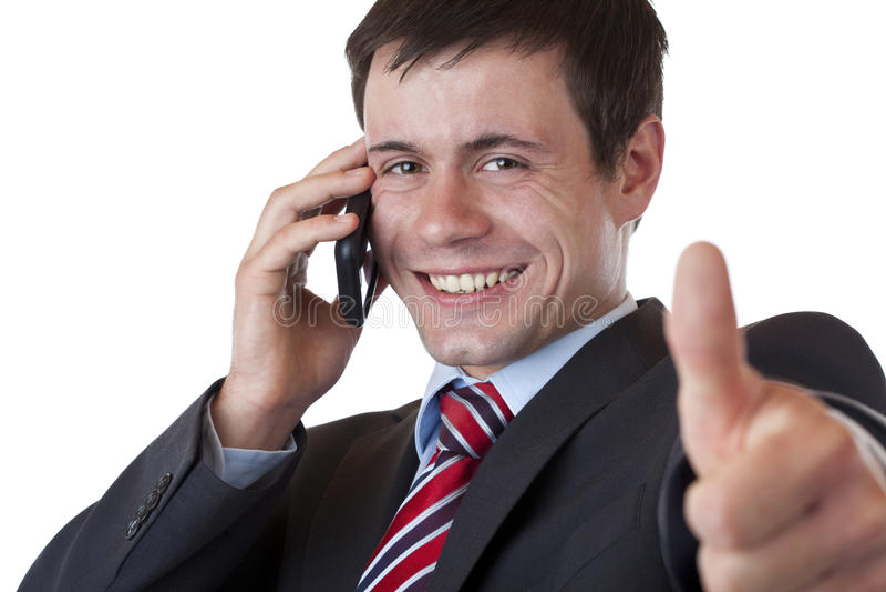 Homem de negócios que faz um atendimento de telefone que mostra o polegar acima fotos de stock royalty free