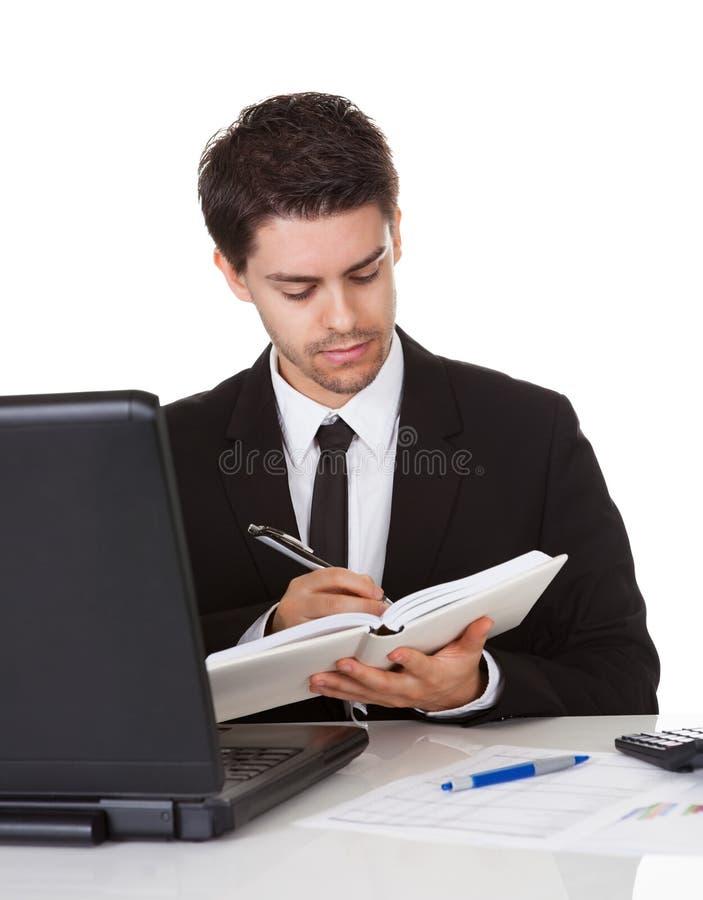 Homem de negócios que faz uma anotação em seu diário fotografia de stock