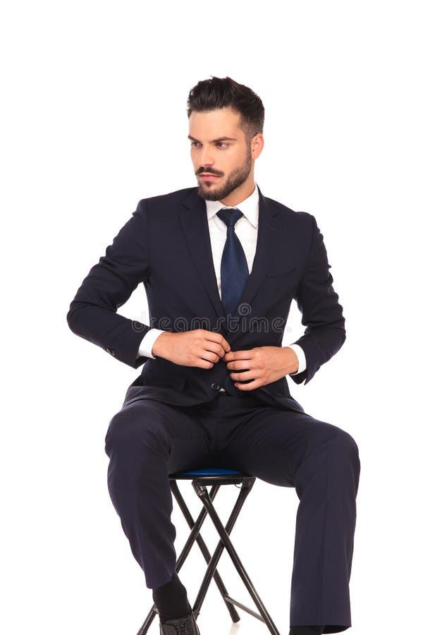 Homem de negócios que fecha seus terno e olhares para tomar partido ao sentar-se imagens de stock royalty free