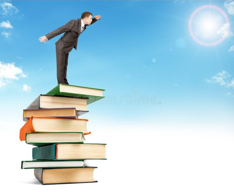 Homem de negócios que fica na pilha dos livros no céu imagem de stock royalty free