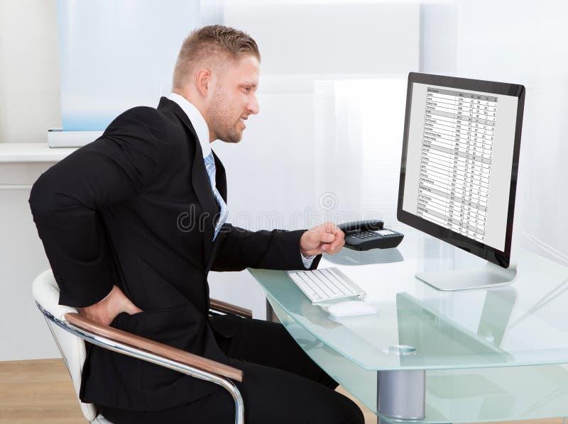 Homem de negócios que fricciona o seu traseiro como senta o trabalho em sua mesa foto de stock