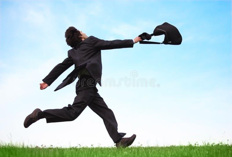 Homem de negócios que funciona no prado com saco foto de stock