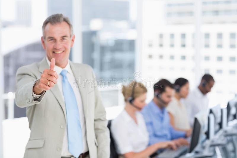 Homem de negócios que gesticula os polegares acima com os executivos que usam computadores fotos de stock royalty free