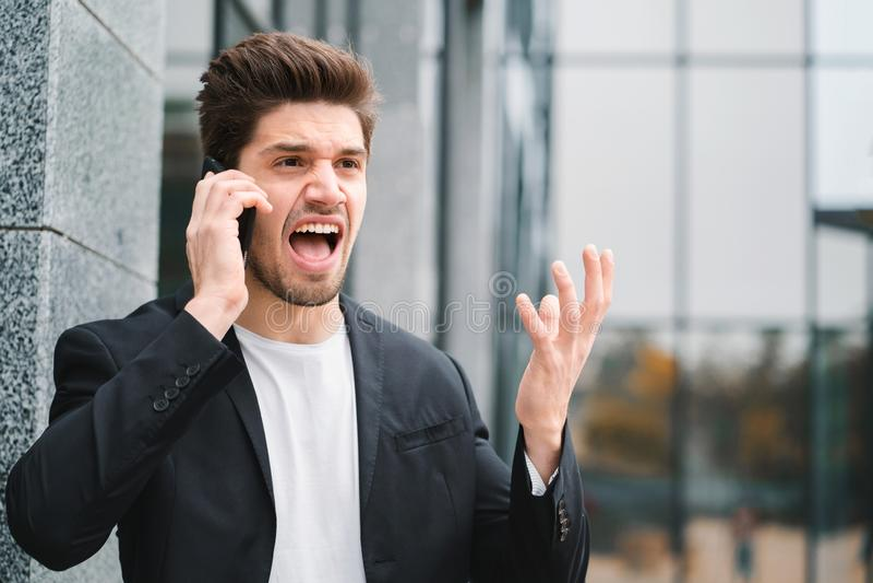 Homem de negócios que grita no telefone celular Tendo a divisão nervosa no trabalho, gritando na raiva, gestão de tensão, mental fotografia de stock royalty free
