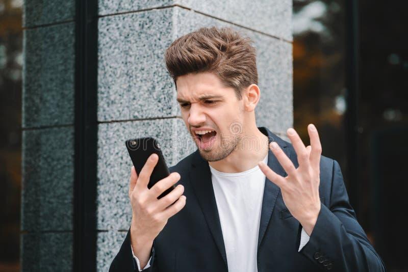 Homem de negócios que grita no telefone celular Tendo a divisão nervosa no trabalho, gritando na raiva, gestão de tensão, mental imagens de stock royalty free