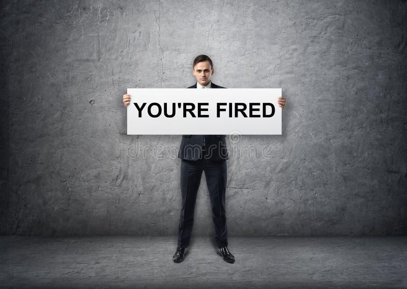 Homem de negócios que guarda a bandeira com & o x27; you& x27; re fired& x27; texto nele em suas mãos foto de stock