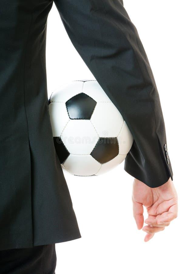 Homem de negócios que guarda a bola de futebol fotografia de stock