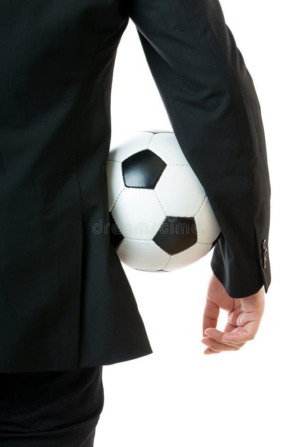 Homem de negócios que guarda a bola de futebol imagem de stock royalty free