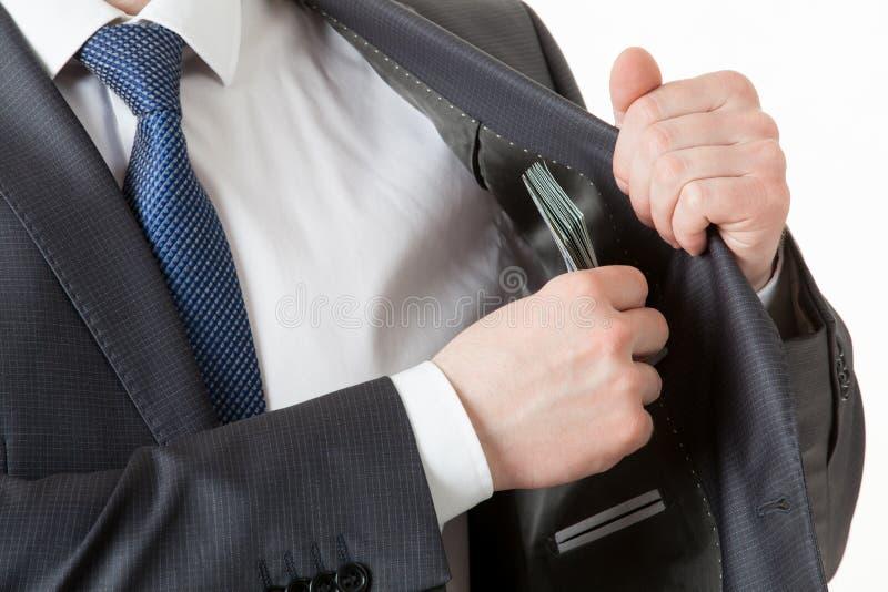 Homem de negócios que guarda a colocação de dólares em um bolso fotos de stock