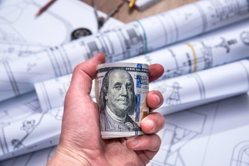 Homem de negócios que guarda dólares acima da máquina de desenho fotos de stock