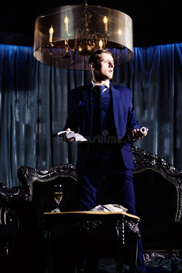 Homem de negócios que guarda dólares do dinheiro do dinheiro em suas mãos foto de stock royalty free