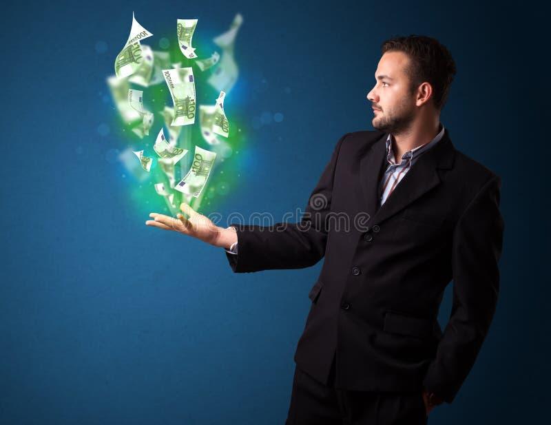 Homem de negócios que guarda dinheiros de papel de incandescência imagens de stock royalty free